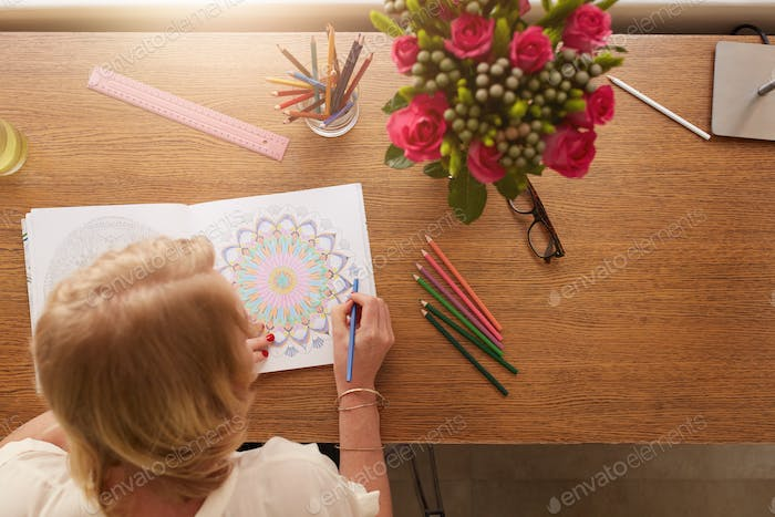 Woman drawing in adult coloring book