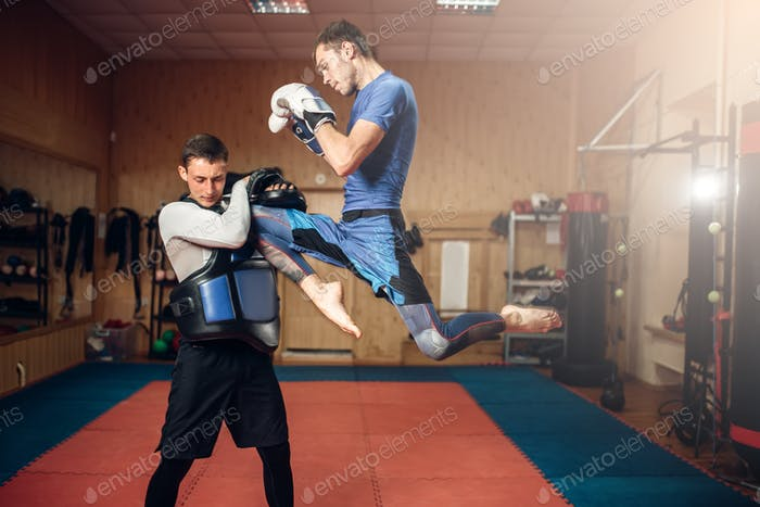 Male kickboxer doing kick in jump, kickboxing