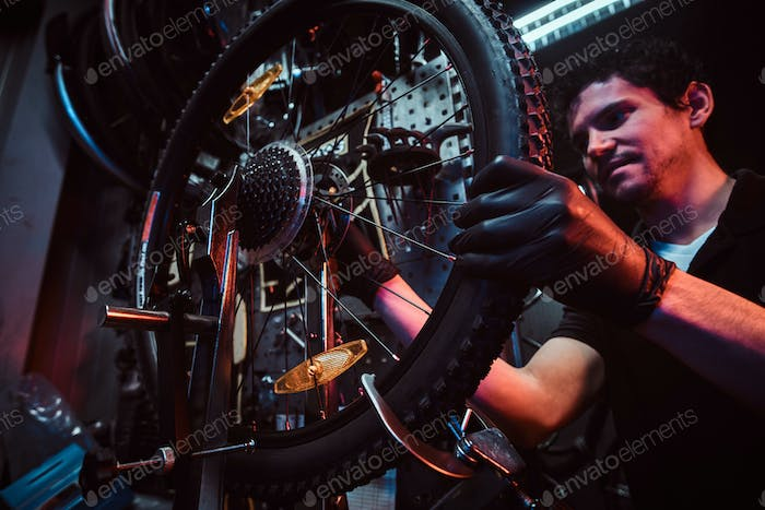 Diligent attractive mechanic is fixing bicycle at his own workshop