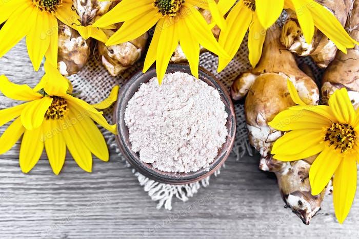 Flour of Jerusalem artichoke in bowl on board top
