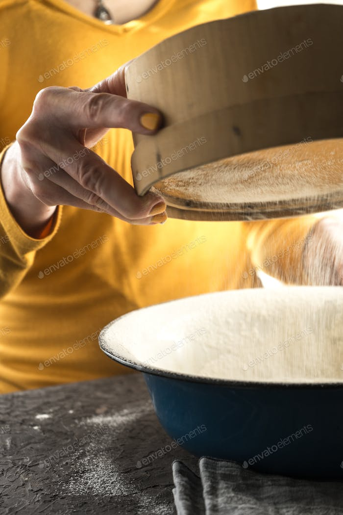 White flour is sieved into a large blue bowl with a free space