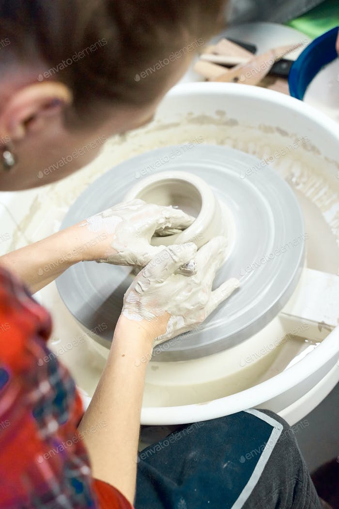 Woman making ceramic pottery on wheel, hands closeup. Concept for woman in freelance