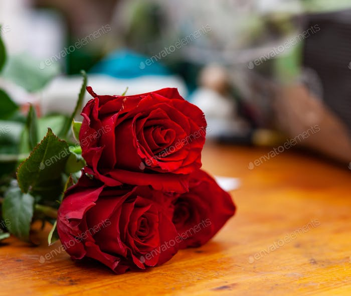 Red roses are on the counter in the flower shop.