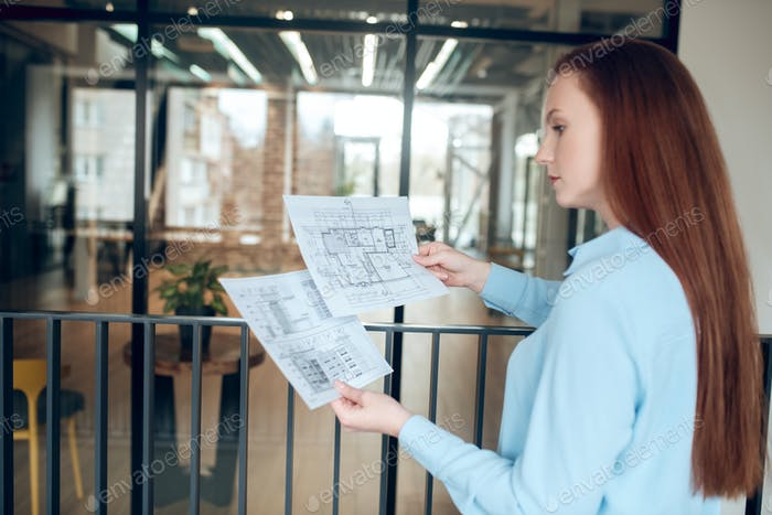 Serious woman pondering over building plan