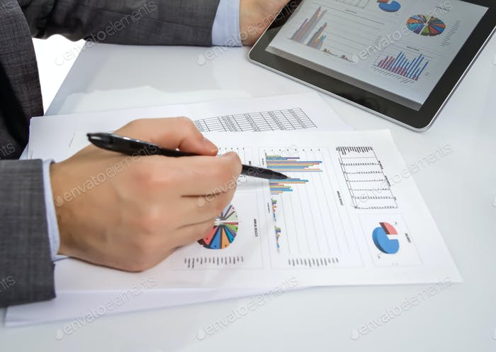 Businessman reviewing documents in digital tablet