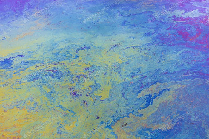 Spilled diesel fuel on surface on ocean water, close up, blue and yellow patterns.