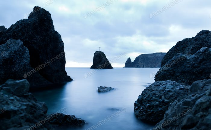 Still sea waters, harsh rocks and cross on rock peak in evening on summer day with gloomy sky at