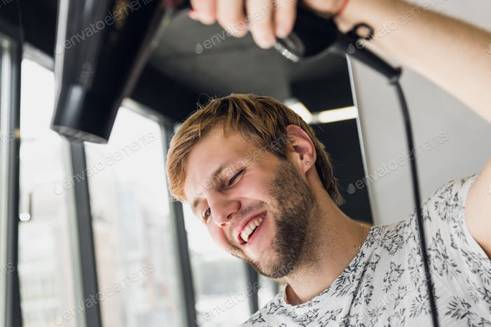Portrait of happy hairdresser holding comb and blow dryer in salon