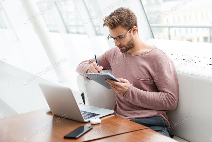 Image of man using laptop and clipboard while working in cafe indoors