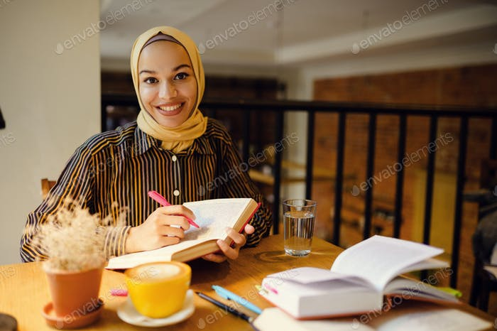 Smiling arab girl in hijab holds notebook