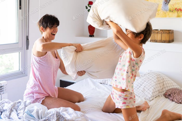 Mother and daughter having funny pillow fight on bed