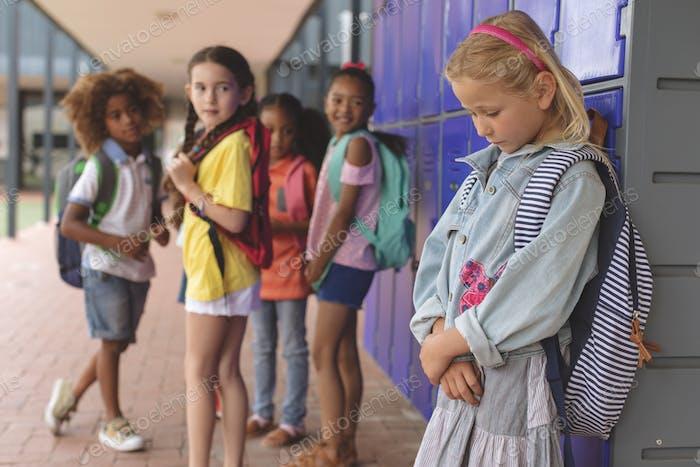 Sad schoolgirl standing in corridor