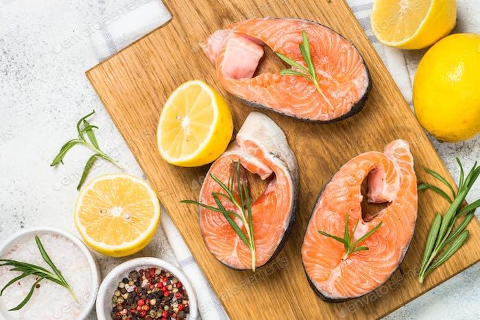 Raw salmon steak on white top view