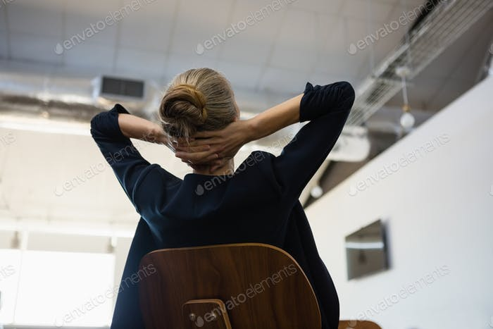 Businesswoman with hands behind head relaxing at office