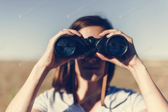 Traveler spying through binoculars