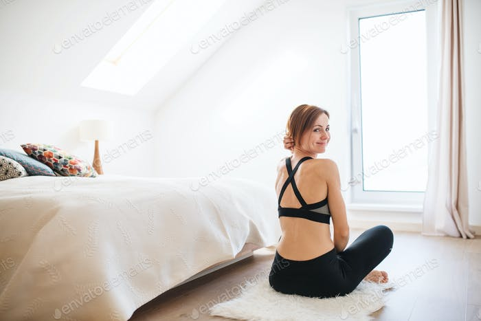 A young woman doing yoga exercise indoors in a bedroom. Copy space.