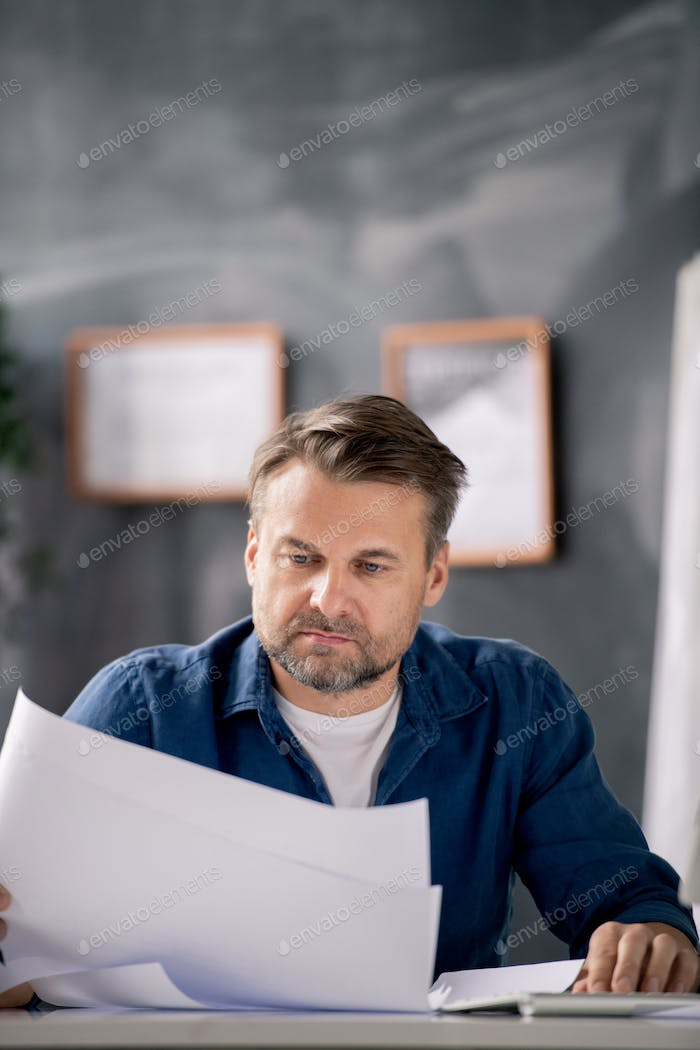 Bearded middle aged architect in casualwear looking at blueprint with sketch