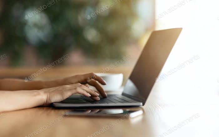 Unrecognizable woman typing on laptop at cafe