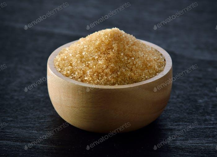 Zucker in Holzschale auf schwarzem Holz