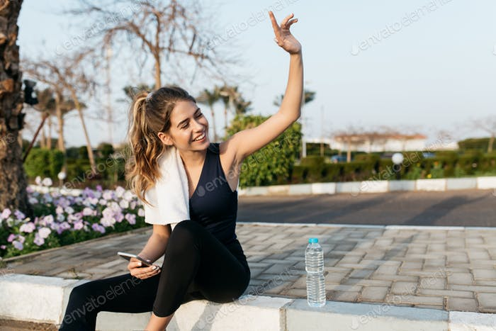 Excited joyful young woman in sportswear gratulating to side in sunny morning. Expressing positivity