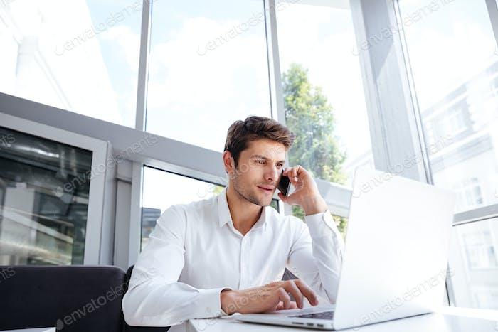 Hombre de Empresario hablando por teléfono celular y Uso Ordenador portátil en la oficina