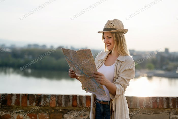 Tourist woman looking at map and exploring city