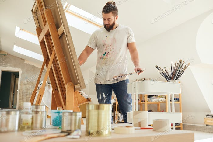 Mature Male Artist Painting Picture in Studio