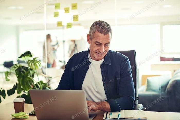 Sonriente Empresario maduro leyendo su horario y el Uso un Ordenador portátil