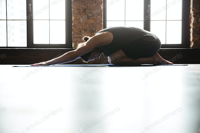 Sporty healthy man stretching back before gym workout