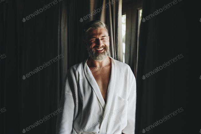 Cheerful man in a bathrobe