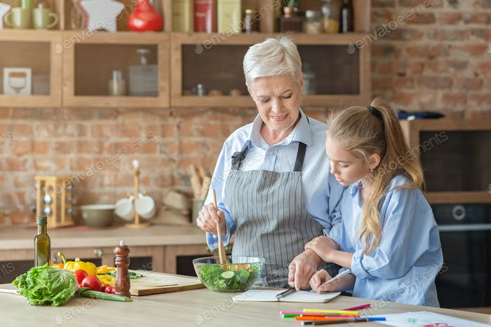Granny teaching her granddaughter cooking in kitchen