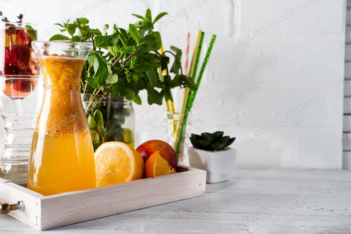 Orange lemonade in the decanter on a wooden tray with ftuits and mint