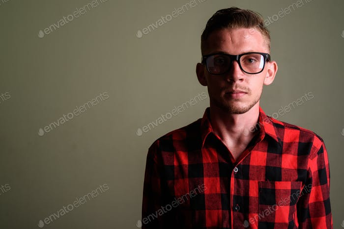 Young man wearing red checkered shirt against colored background