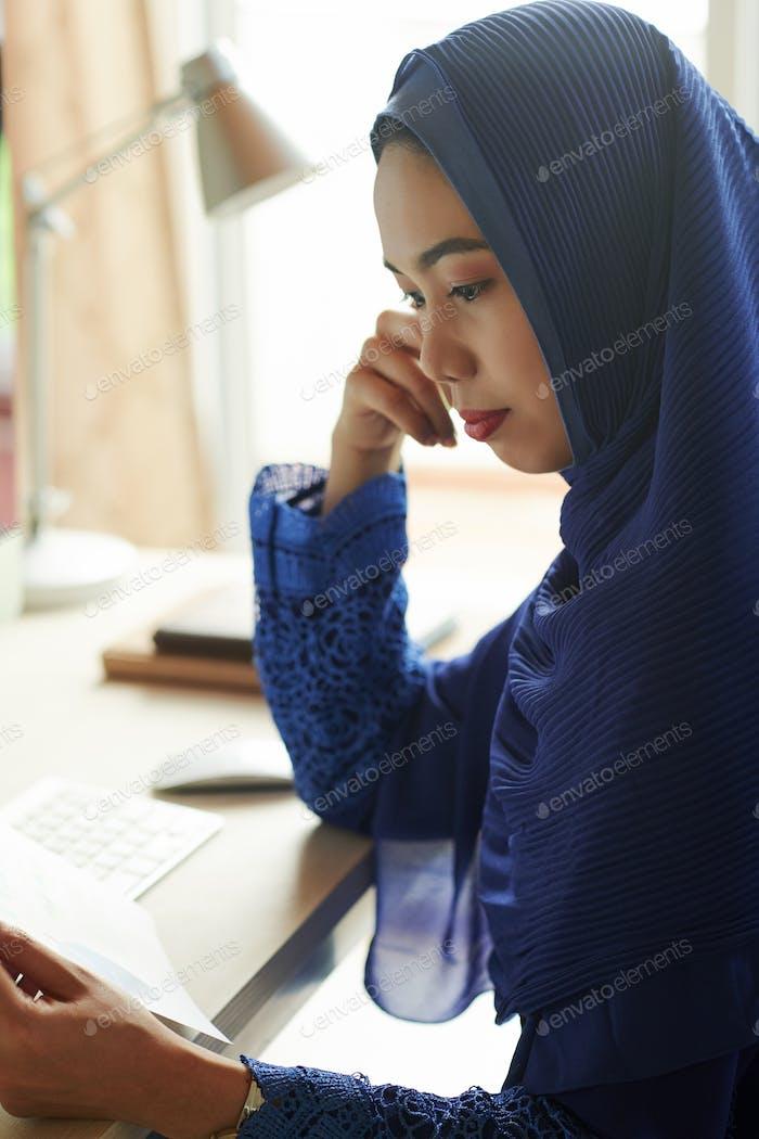 Muslim woman reading document