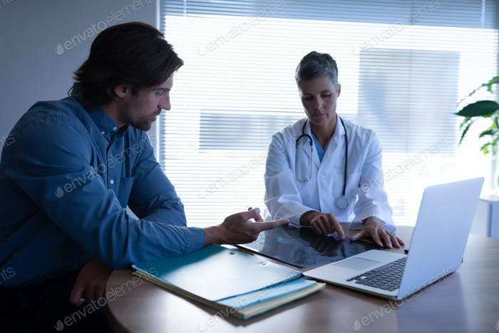 Female doctor and Caucasian patient discussing over x-ray in clinic at hospital