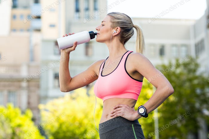 A beautiful woman drinking water on a sunny day