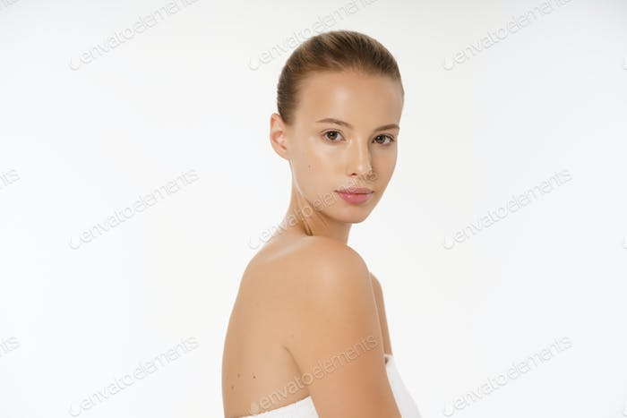 Beautiful girl with nude make up posing at white grey studio background, beauty photo concept