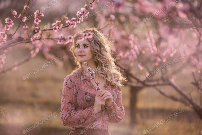 young woman stands in blooming gardens, holds twig with pink inflorescences