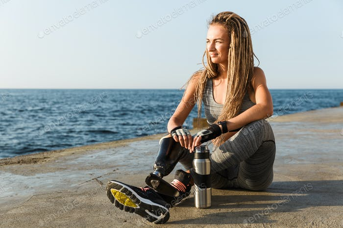 Happy disabled athlete woman with prosthetic leg