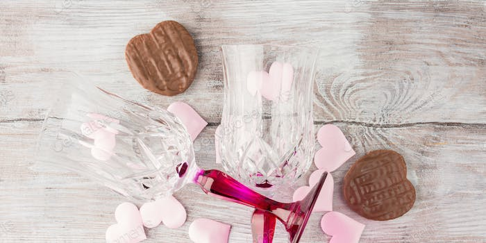 Two stemmed glasses with hearts and chocolate. Banner