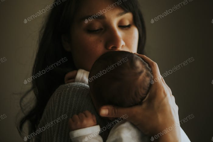Mother holding her baby indoors