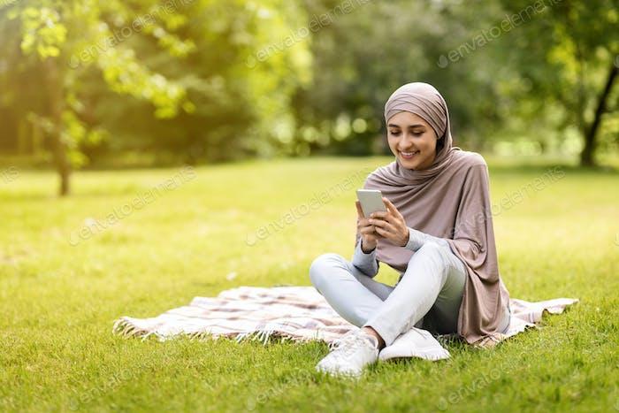 Cheerful muslim girl looking at smartphone screen