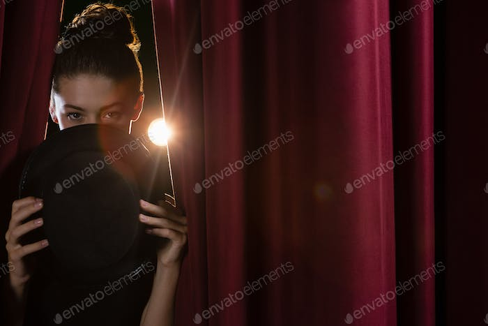 Ballet dancer with hat peeking through a stage curtain