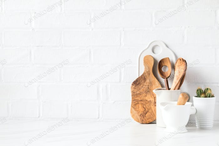 Kitchen utensils on a background of a white brick wall. Concept of the decor of the kitchen.