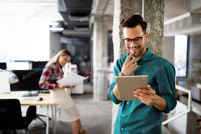 Young man using technology, digital tablet in corporate business office