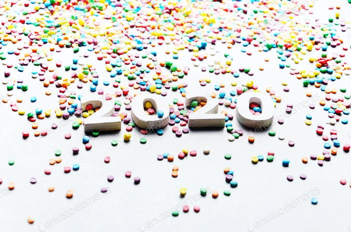 White numbers 2020 with color sugar sprinkles on stone table
