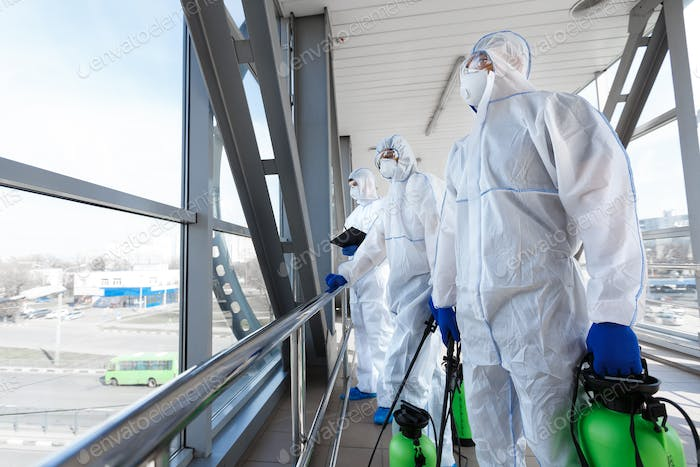 Medical workers in hazmat suits disinfecting with spray public places