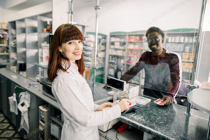 Adult African man client is asking young Caucasian woman pharmacist about medicines near cashbox in