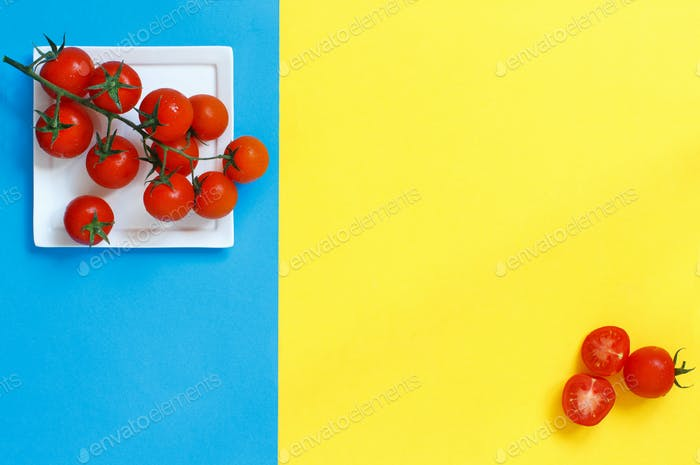 Cherry tomatoes on a blue and yellow background