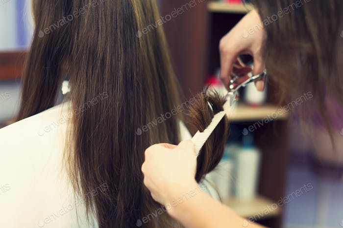 Close up of long hair cut by hairdresser